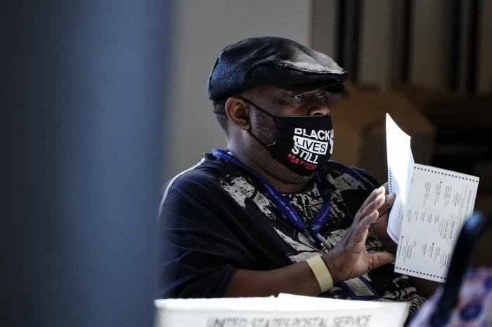 An election worker holds a ballot as vote counting in the general election continues at State Farm Arena in Atlanta.
