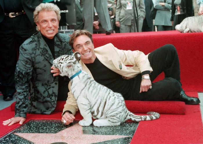 Illusionists Siegfried Fischbacher, left and Roy Uwe Ludwig Horn pose for photographers with a white tiger cub after they unveiled their star on the Hollywood Walk of Fame in Los Angeles, Calif.